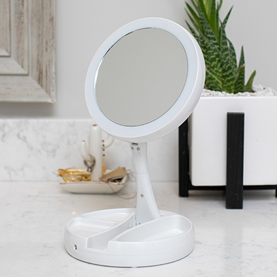 VIVITAR<sup>&reg;</sup> Fold-Away Vanity Mirror - This double sided mirror allows you a close up with 1x and 10x magnification.  Features include smart foldable design for easy traveling and storage, compartments for accessories and cosmetics, adjustable height and angle up to 11&quot; and ultra bright LED illumination.  Works with 4AA batteries (not included).  Mirror dimensions: 2.25&quot; X 6.25&quot;.